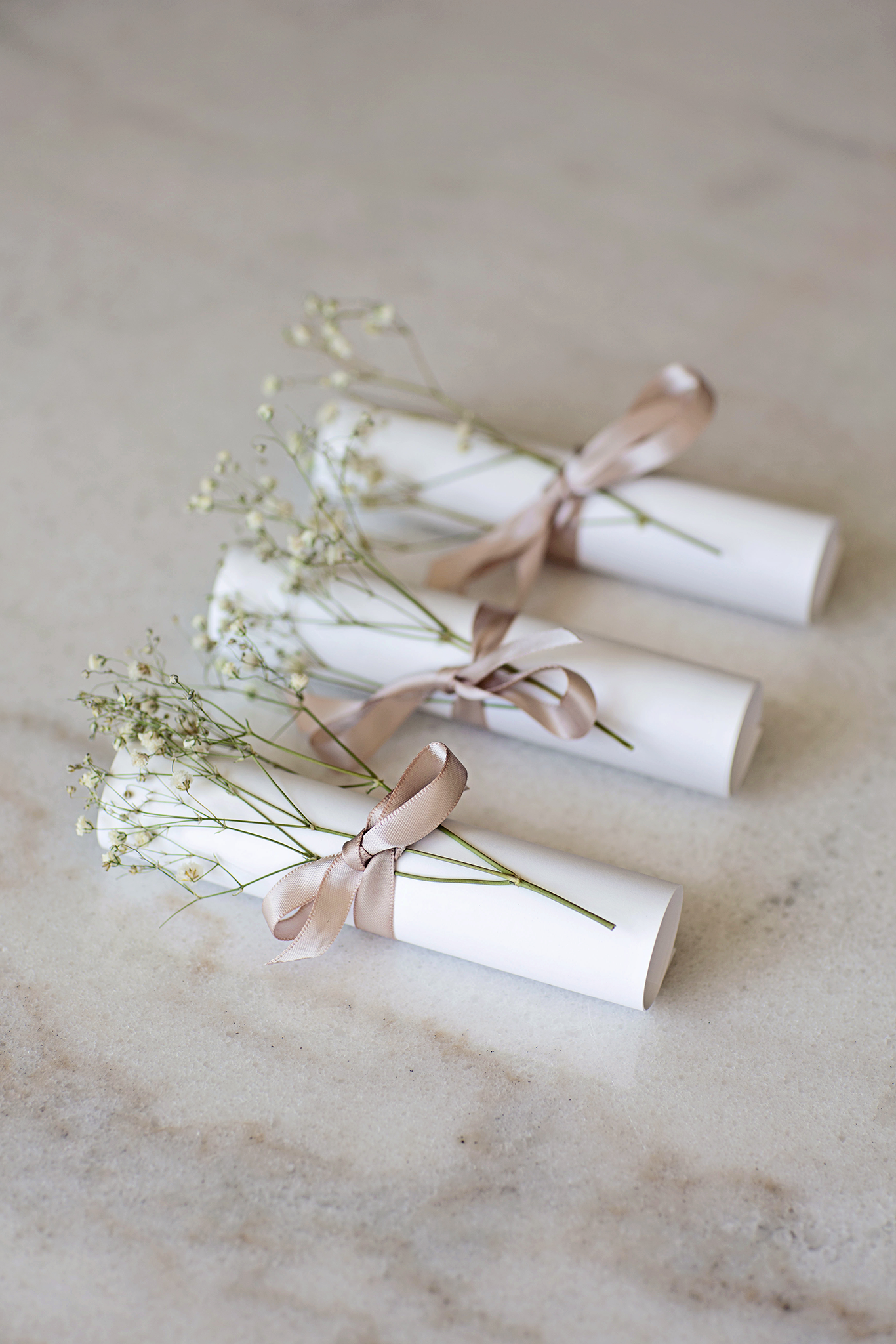 Letters rolled into scrolls, with ribbon and dried flowers